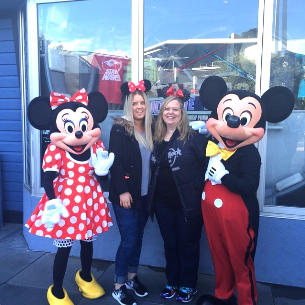 2 beautiful women taking a souvenir photo with Mickey and Minnie