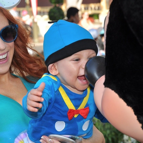 Beautiful baby and his mom smilling and huging Mickey at the Park on July 8 2014