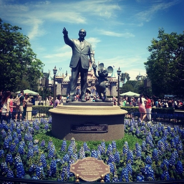 Walt and Mickey at Disneyland Resort with blue sky and blue flowers